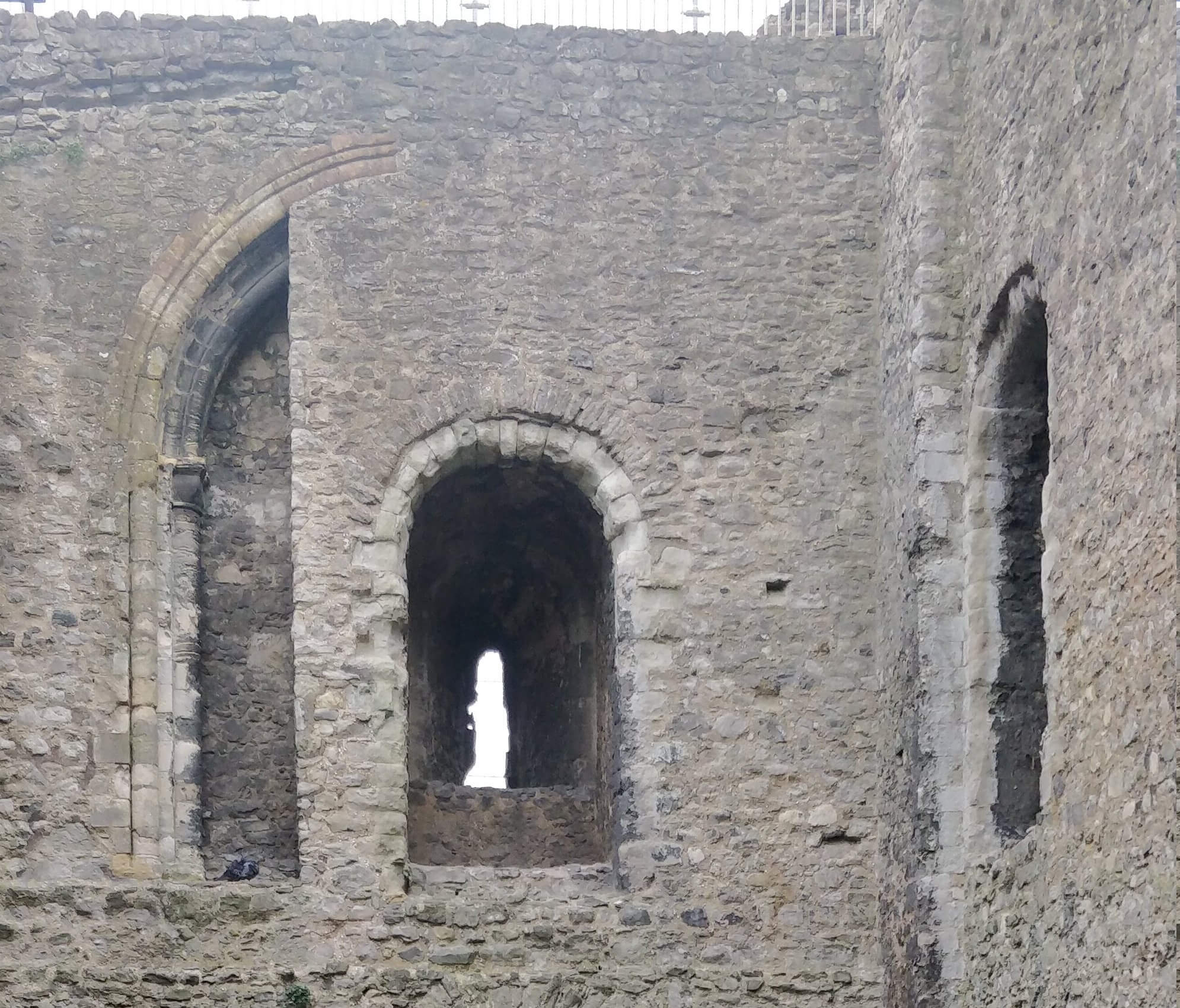 Two windows at the south east corner of the keep. One of them has a larger arch over it which abruptly stops where the wall has been filled in.